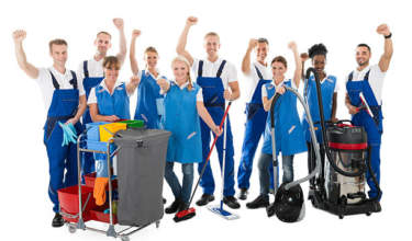 Portrait of happy multiethnic janitors with arms raised holding cleaning equipment against white background